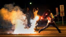 Photojournalist Robert Cohen catches a Ferguson protester throwing a tear gas canister back at police (Aug 2014)